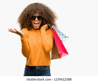 African american woman holding shopping bags very happy and excited, winner expression celebrating victory screaming with big smile and raised hands
