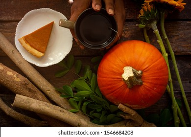 an african american woman holds a warm mug of tea next to a pumpkin pie and three yellow flowers and a stack of wooden branches an orange pumpkin on top of a wooden table
