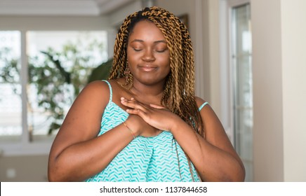 African american woman at home smiling with hands on chest with closed eyes and grateful gesture on face. Health concept.