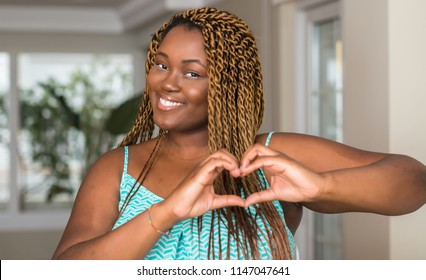 African american woman at home smiling in love showing heart symbol and shape with hands. Romantic concept.