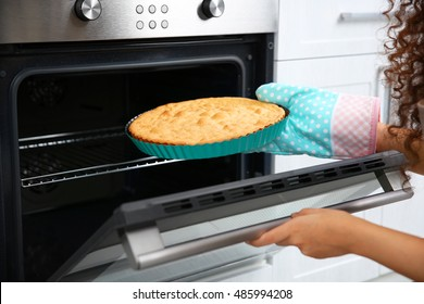 African American woman with hot cake near oven in kitchen