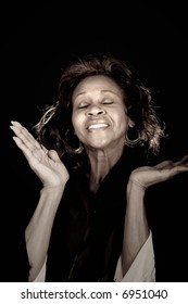 african american woman lifting hands and praising God, over black