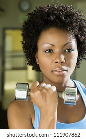 African American woman lifting weights at a gym