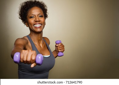 African American woman lifting weights.
