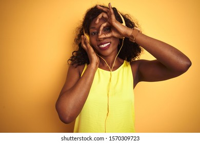 African american woman listening to music using headphones over isolated yellow background with happy face smiling doing ok sign with hand on eye looking through fingers