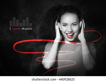 African American woman listening to music in headphones on black background