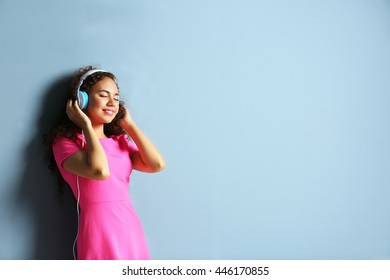 African American woman listening to music in headphones on grey background