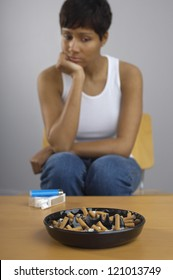 African American woman looking at full ashtray on table