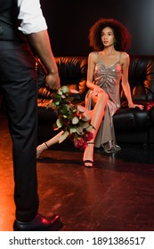 african american woman looking at man with roses on black and blurred foreground