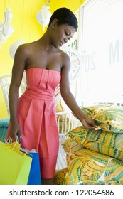 African American woman looking at price tag of cushion at home decor store