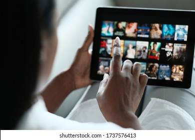 African American Woman Lying Down On Sofa At Home, Choosing Movie On Internet Streaming Service. Over The Shoulders. - Shutterstock ID 1737576413