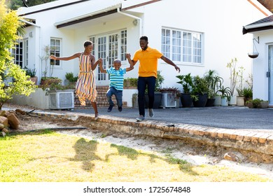African American woman, man and their son, spending time together in their garden. Social distancing and self isolation in quarantine lockdown for Coronavirus Covid19