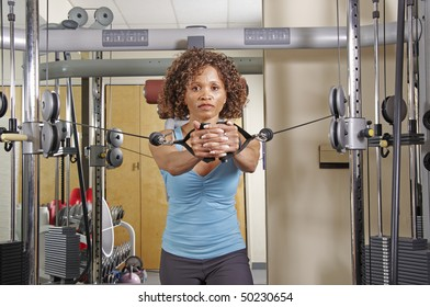 An African American woman in the middle of a standing row exercise in the gym