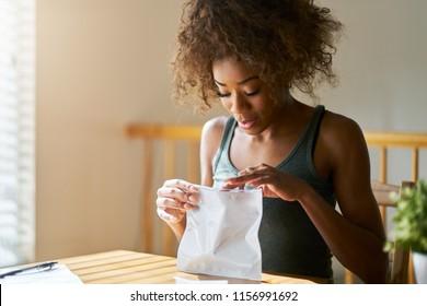 african american woman opening bag of legal marijuana from dispensary