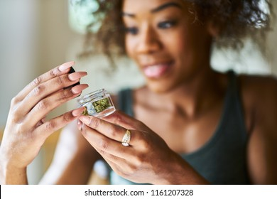 african american woman opening bottle of legal marijuana from dispensary close up