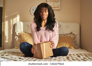 african american woman opening box on bed