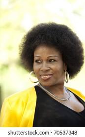 African American Woman outdoor portrait black dress yellow jacket