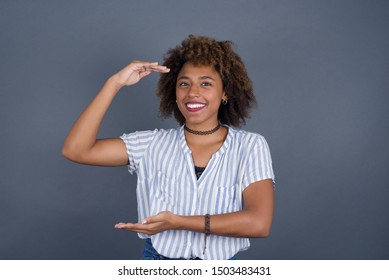 African American woman over isolated background gesturing with hands showing big and large size sign, measure symbol. Smiling looking at the camera. Measuring concept.