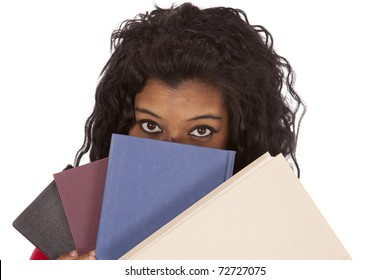 An African American woman is peaking out from behind a stack of books.
