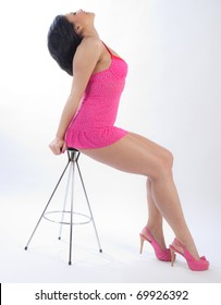 African American woman in pink lingerie on stool
