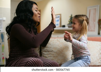 African American woman playing with girl.