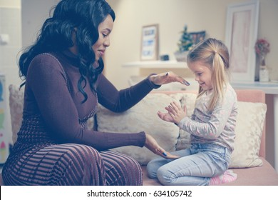 African American woman playing with girl. Woman plating wit her adopted daughter.