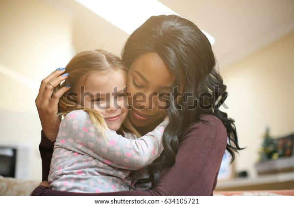 African American woman playing with girl. Woman hugging her adopted daughter.