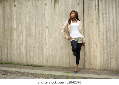 African American woman posing in front of concrete wall