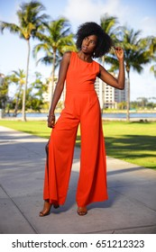 African American woman posing in an orange dress at the park
