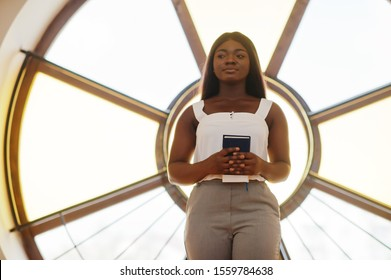 African american woman praying in the church. Believers meditates in the cathedral and spiritual time of prayer. Afro girl with bible against large round window.