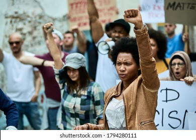 African American woman with raised fist participating in black civil rights demonstrations.