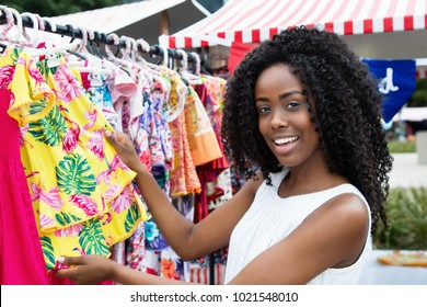 African american woman selling colorful clothes outdoors at typical traditional market