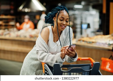 African american woman with shopping cart trolley in the supermarket store look on mobile phone.