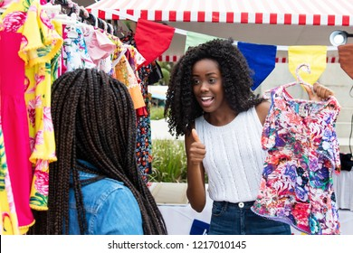 African american woman showing colorful clothes to buyer at typical market