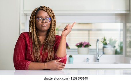 African american woman sitting at home very happy pointing with hand and finger to the side