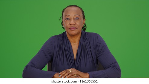 African American woman sitting and looking at camera on green screen
