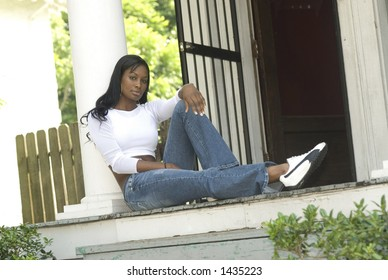 african american woman sitting on the porch of an older home - urban setting