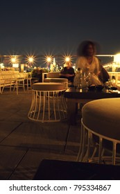 African American woman sitting on a chic rooftop bar at night in Manhattan. Stools and table, large string lights along the balcony, lights of New York City in the background, shutter drag.