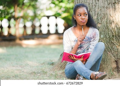 African American woman sitting under tree with journal