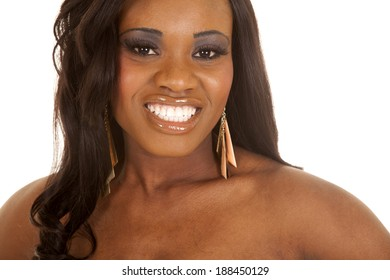 An african American woman with a smile and bare shoulders.