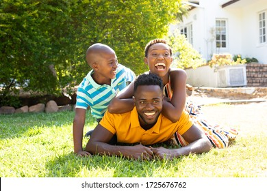 African American woman spending time with her partner and their son, lying on a lawn in the garden. . Social distancing and self isolation in quarantine lockdown for Coronavirus Covid19