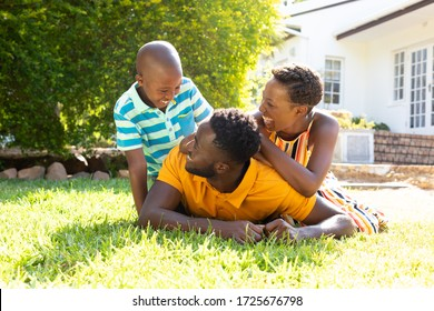 African American woman spending time with her partner and their son, lying on a lawn in the garden. Social distancing and self isolation in quarantine lockdown for Coronavirus Covid19