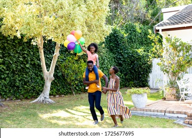 African American woman spending time with her partner who is giving their daughter a piggyback in the garden. Social distancing and self isolation in quarantine lockdown.