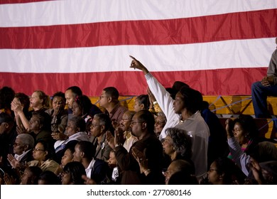African American woman standing in front of American Flag at Barack Obama Presidential Rally, October 29, 2008 in Rocky Mount High School, North Carolina