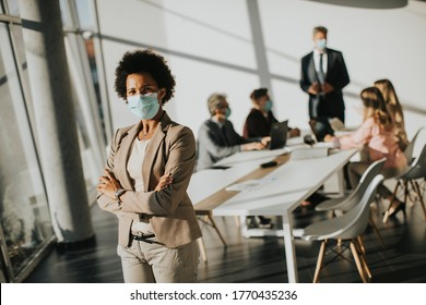 African American woman standing in the office and wear mask as protection from corona virus