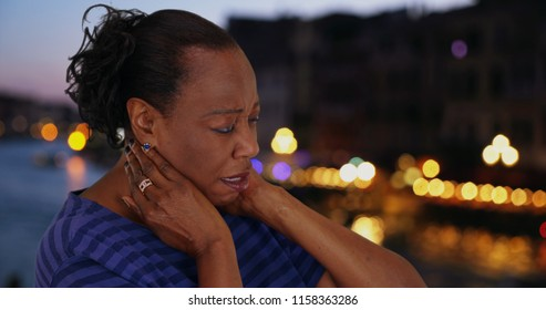 African American woman standing outdoors at night has bad neck pain