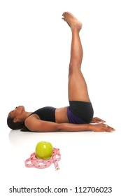 African American woman stretching with apple and measuring tape in foreground - with selective focus on front