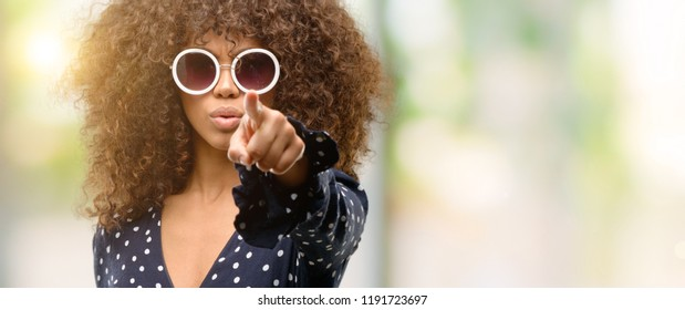 African american woman with sunglasses and summer dress pointing with finger to the camera and to you, hand sign, positive and confident gesture from the front