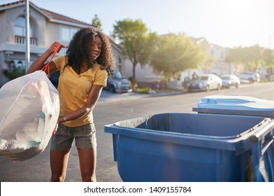 african american woman taking out the tash in las vegas neighborhood,