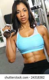 african american woman training or exercising in gym, doing weight lifting